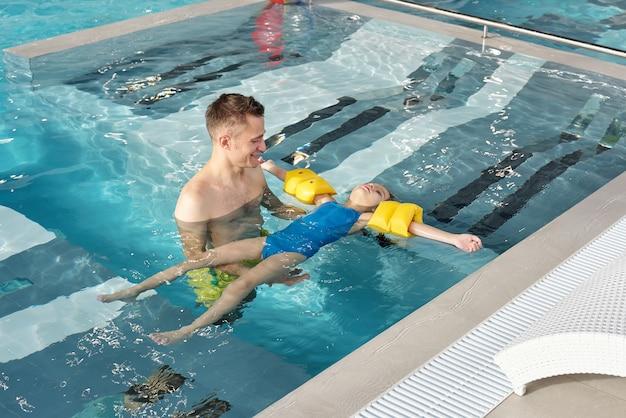 Счастливый молодой человек поддерживает свою маленькую дочь в защитных рукавах во время плавания в бассейне с прозрачной водой в современном спа-центре