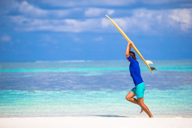 Happy young man surfing on the tropical coast