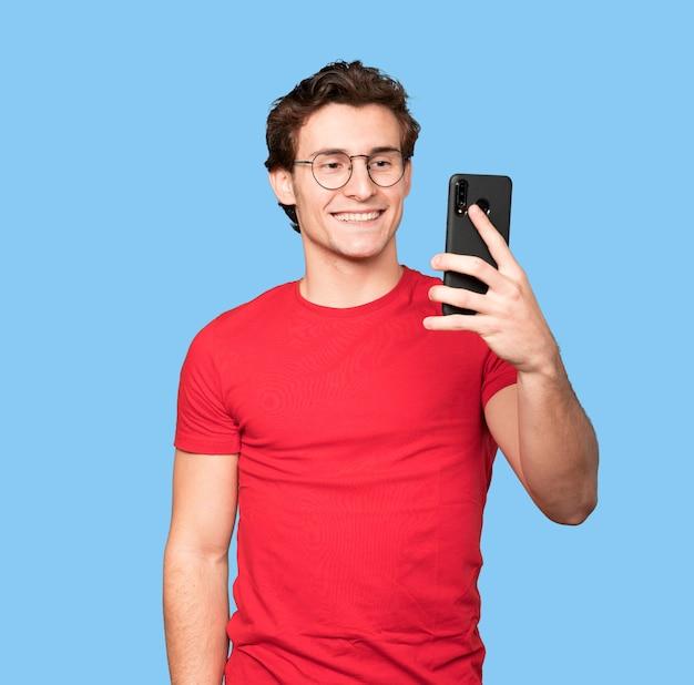Счастливый молодой человек, делающий селфи со своим мобильным телефоном