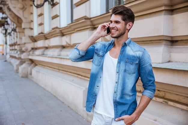 Счастливый молодой человек разговаривает по мобильному телефону на улице