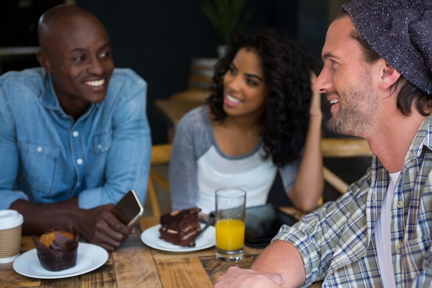 Happy young man talking with friends at table in coffee house