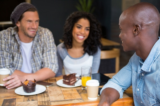 Happy young man talking with friends at table in coffee shop