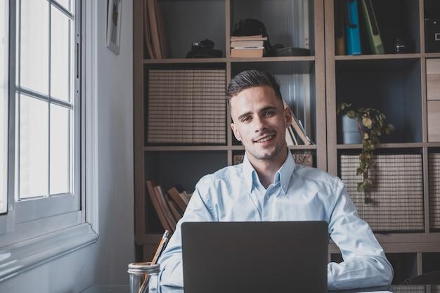 Счастливый молодой человек подросток улыбается и разговаривает в видеоконференции, изучая и обучаясь онлайн со школой. миллениалы делают домашнее задание по телефону
