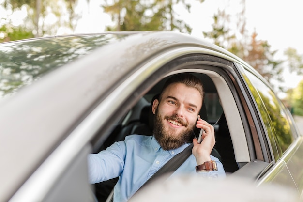 Happy young man traveling by car using mobile phone