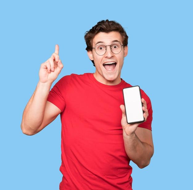 Счастливый молодой человек с помощью мобильного телефона и указывая вверх