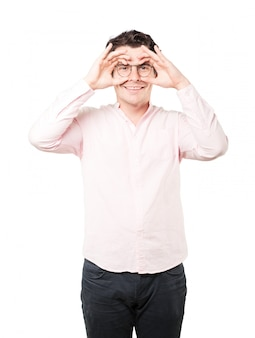 Happy young man using his hands like a binoculars