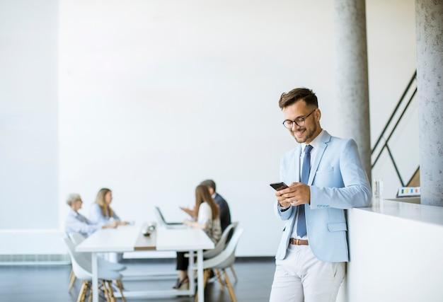 Счастливый молодой человек с помощью своего мобильного телефона в офисе и улыбается, пока его коллеги работают