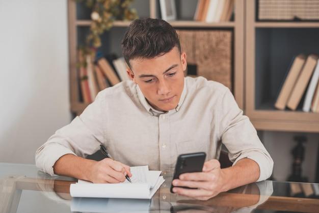 Счастливый молодой человек с помощью своего смартфона дома, серфинг в сети, делать домашнее задание, развлекаясь в одиночестве в помещении. подросток мужского пола с телефоном в свободное время учится и работает.