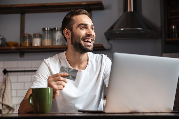 台所のテーブルに座って、クレジットカードを表示しながらラップトップコンピューターを使用して幸せな若い男