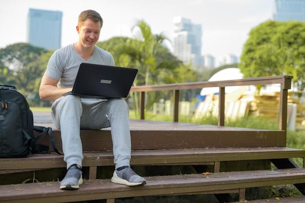 공원에서 나무 다리에 노트북을 사용 하여 행복 한 젊은 사람