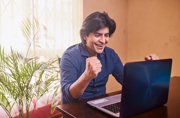 デスクでラップトップまたはコンピューターを使用して幸せな若い男。