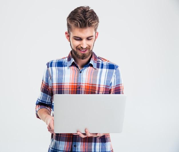 Счастливый молодой человек с помощью ноутбука