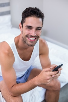 Happy young man using mobile phone on bed