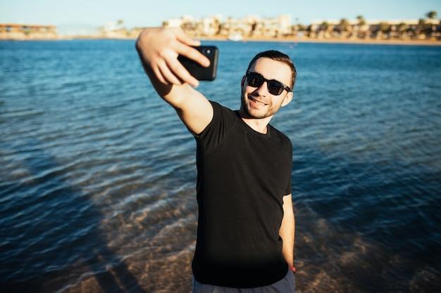 Giovane felice in vacanza a ridere in spiaggia prendendo selfie in occhiali da sole sul mare