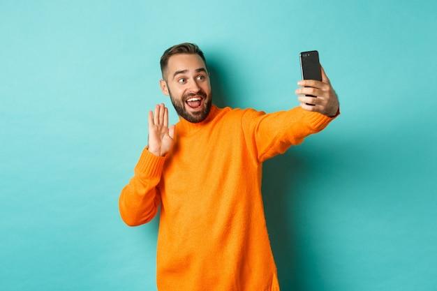 幸せな若い男のビデオ通話、携帯電話でオンラインで話し、スマートフォンのカメラに挨拶し、手を優しい手を振って、明るいターコイズブルーの壁の上に立っています。