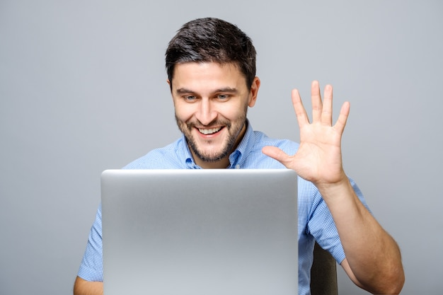 Happy young man video chatting on laptop computer