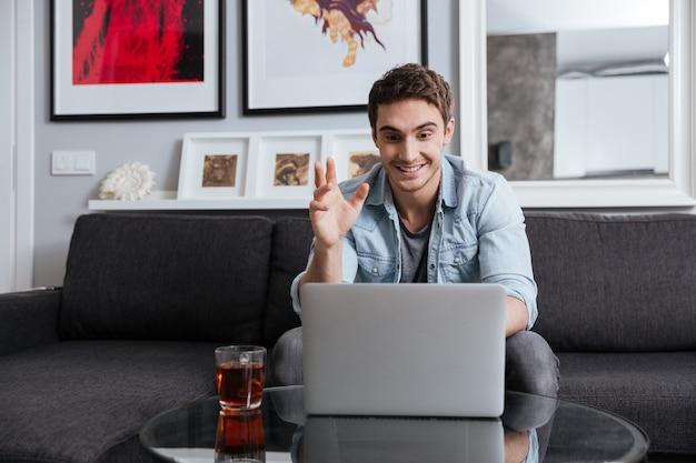 自宅のソファに座ってラップトップコンピューターで幸せな若い男のビデオチャット