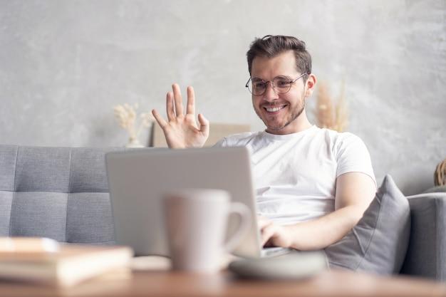 집에서 소파에 앉아있는 동안 랩톱 컴퓨터에서 행복 한 젊은 남자 비디오 채팅