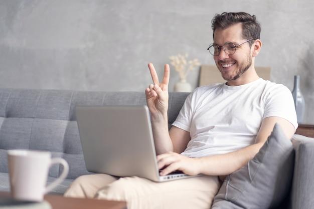 Счастливый молодой человек видео-чате на портативном компьютере, сидя на диване у себя дома