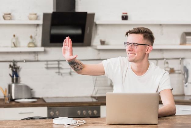 Happy young man waving his hand with laptop on table in the kitchen