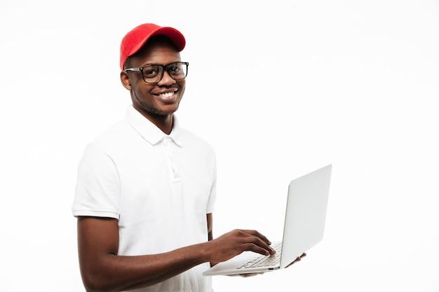 Protezione da portare felice del giovane per mezzo del computer portatile