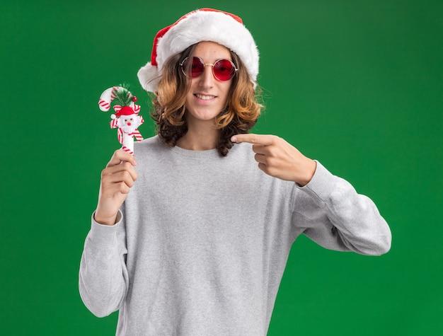 Счастливый молодой человек в рождественской шляпе санта-клауса и красных очках держит рождественскую конфету, глядя в камеру, улыбаясь, указывая указательным пальцем на нее, стоя на зеленом фоне