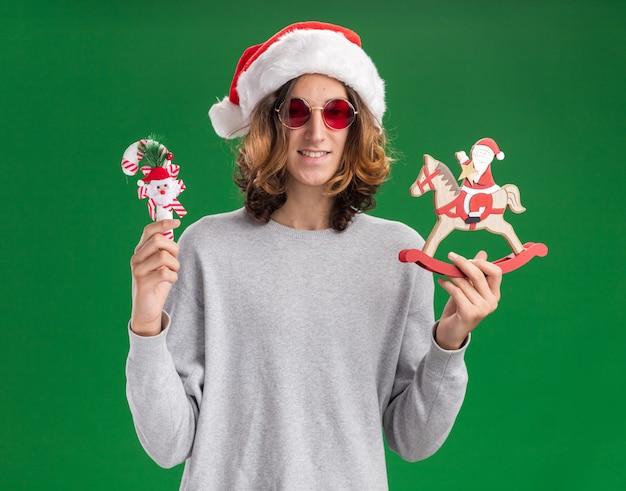 緑の背景の上に立っている顔に笑顔でカメラを見てクリスマスのおもちゃを保持しているクリスマスのサンタの帽子と赤い眼鏡を身に着けている幸せな若い男