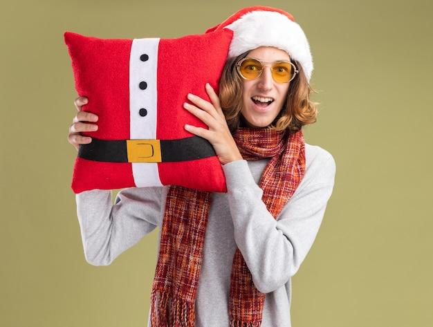 クリスマスのサンタの帽子と彼の首の周りに暖かいスカーフと緑の壁の上に立っている顔に笑顔でクリスマスの枕を保持している黄色いメガネを身に着けている幸せな若い男