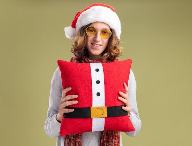 녹색 벽 위에 서있는 얼굴에 미소로 크리스마스 베개를 들고 그의 목에 따뜻한 스카프와 함께 크리스마스 산타 모자와 노란색 안경을 쓰고 행복 한 젊은 남자