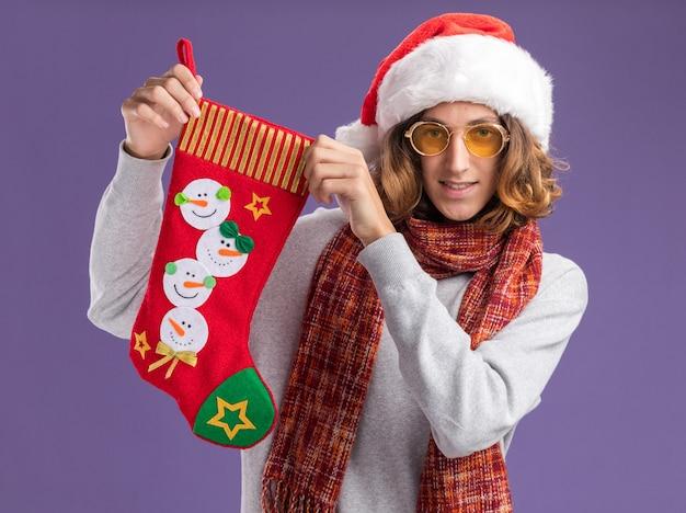 Счастливый молодой человек в рождественской шляпе санта-клауса и желтых очках с теплым шарфом на шее, держащий рождественский чулок, смотрит в камеру с улыбкой на лице, стоя на фиолетовом фоне