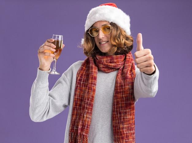 クリスマスのサンタの帽子と黄色いメガネを身に着けている幸せな若い男は、首に暖かいスカーフを持って、紫色の壁の上に立って親指を見せて笑っているシャンパンのガラスを持っています