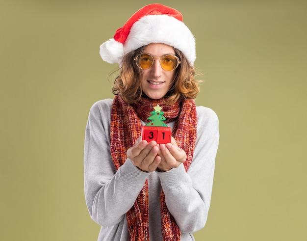 녹색 벽 위에 유쾌하게 서있는 새해 날짜와 장난감 큐브를 들고 그의 목에 따뜻한 스카프와 함께 크리스마스 산타 모자와 노란색 안경을 쓰고 행복 한 젊은 남자