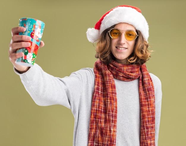 緑の背景の上に元気に立って笑顔のカラフルな紙コップを示す彼の首に暖かいスカーフとクリスマスサンタの帽子と黄色いメガネを身に着けている幸せな若い男