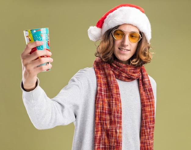 Счастливый молодой человек в рождественской шляпе санта-клауса и желтых очках с теплым шарфом на шее показывает красочный бумажный стаканчик, весело улыбаясь, стоя над зеленой стеной