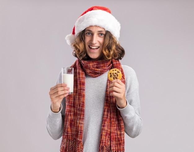首の周りに暖かいスカーフと白い壁の上に元気に立って笑顔のミルクとクッキーのガラスを保持しているクリスマスサンタの帽子をかぶって幸せな若い男