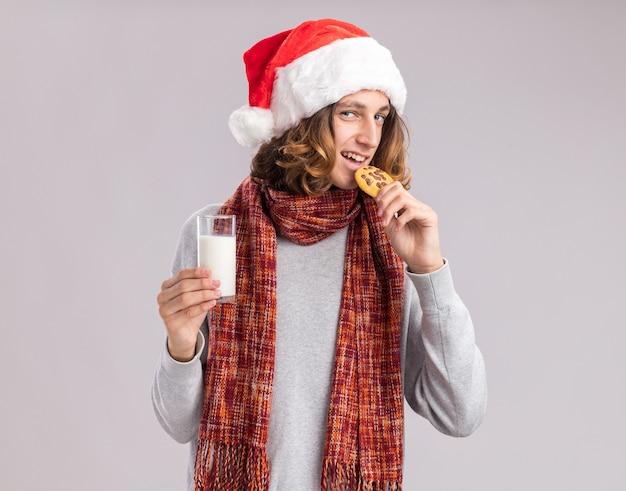 白い壁の上に立っているクッキーを食べる牛乳のガラスを保持している彼の首の周りに暖かいスカーフとクリスマスサンタの帽子をかぶって幸せな若い男
