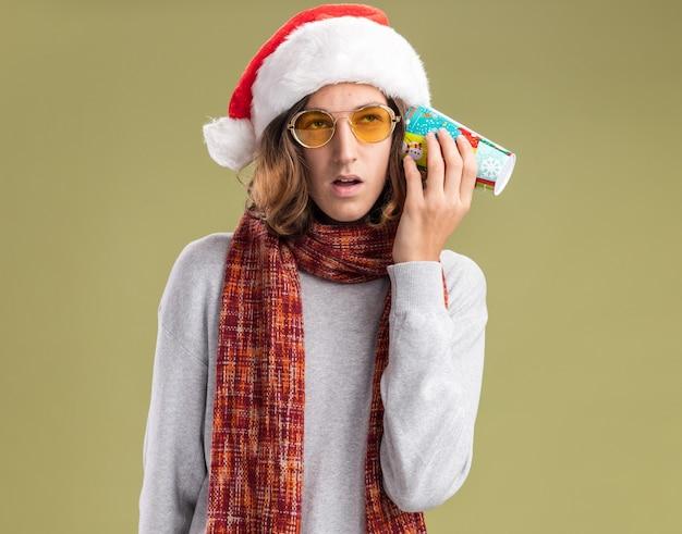 Felice giovane uomo che indossa natale santa cappello e occhiali gialli con calda sciarpa intorno al collo tenendo colorato bicchiere di carta sopra il suo orecchio cercando confuso in piedi su sfondo verde