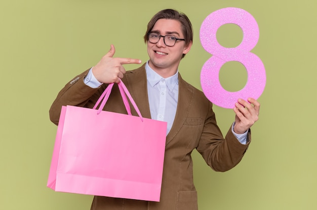Happy young man wearing glasses holding paper bags with gifts and number eight made from cardboard pointing with index finger at it smiling international womens day march concept