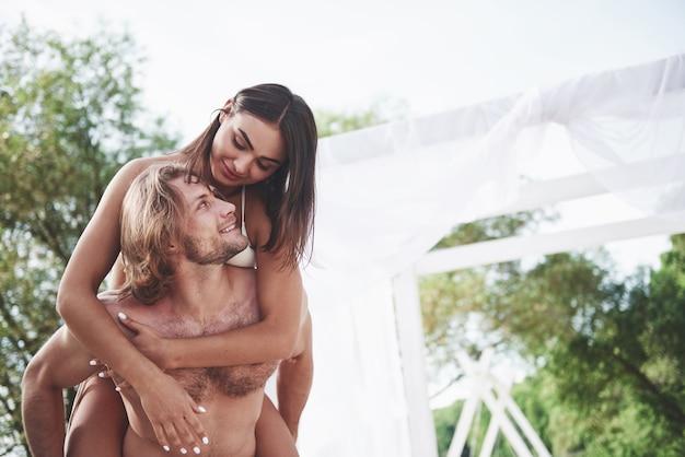 ビーチの肩に彼の妻を着て幸せな若い男。