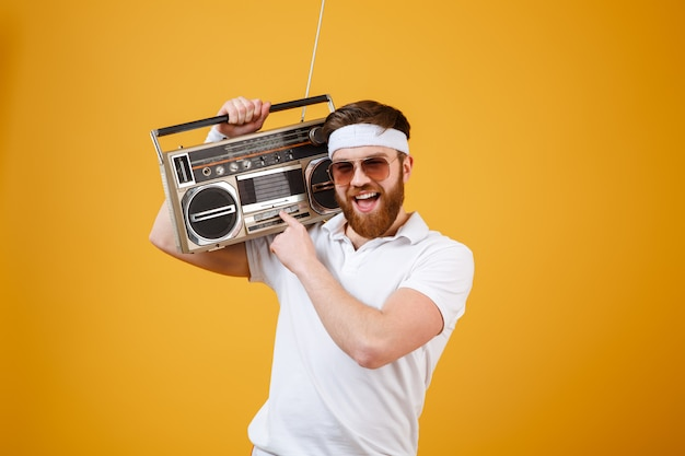 Happy young man wearing sunglasses holding tape recorder