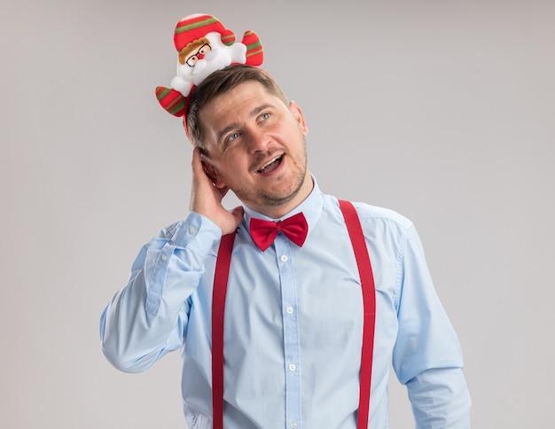 Счастливый молодой человек в подтяжках с галстуком-бабочкой в оправе с санта, глядя с улыбкой на лице, стоящем на белом фоне
