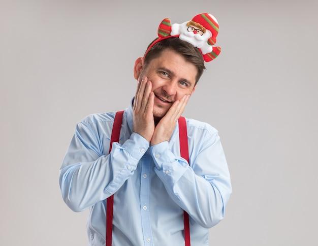 Felice giovane uomo che indossa bretelle farfallino in cerchio con santa guardando la telecamera con un sorriso sul viso in piedi su sfondo bianco