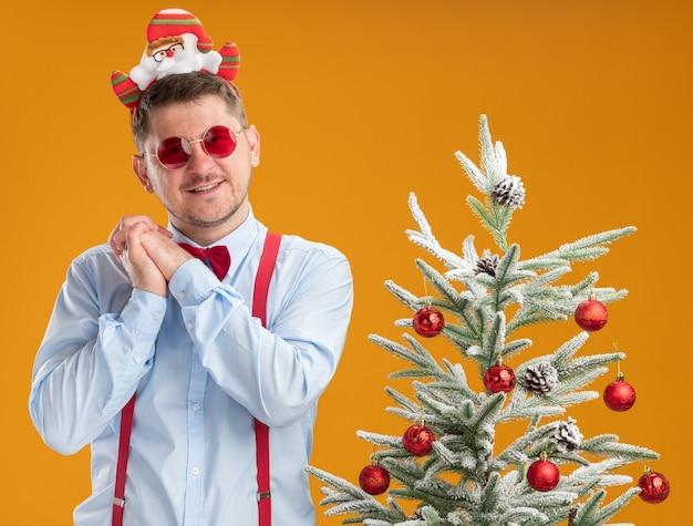Felice giovane uomo che indossa bretelle farfallino nel cerchio con babbo natale e occhiali rossi in piedi accanto all'albero di natale tenendo le mani insieme in attesa di sorpresa su sfondo arancione