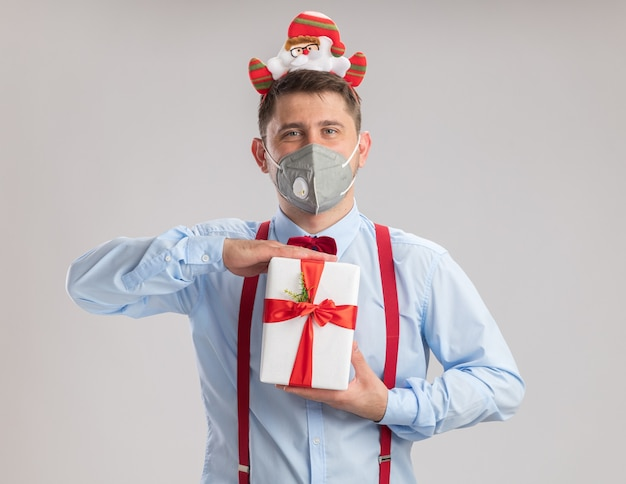 Happy young man wearing suspenders bow tie in rim with santa wearing protective facial mask holding a present looking at camera standing over white background