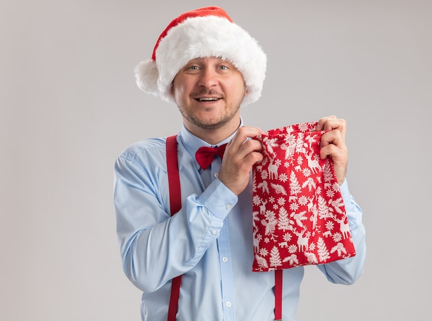 Happy young man wearing suspenders bow tie in santa hat holding red bag full of gifts looking at camera smiling cheerfully standing over white background