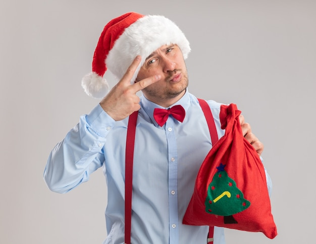 Happy young man wearing suspenders bow tie in santa hat holding santa claus bag full of gifts looking at camera showing v-sign standing over white background