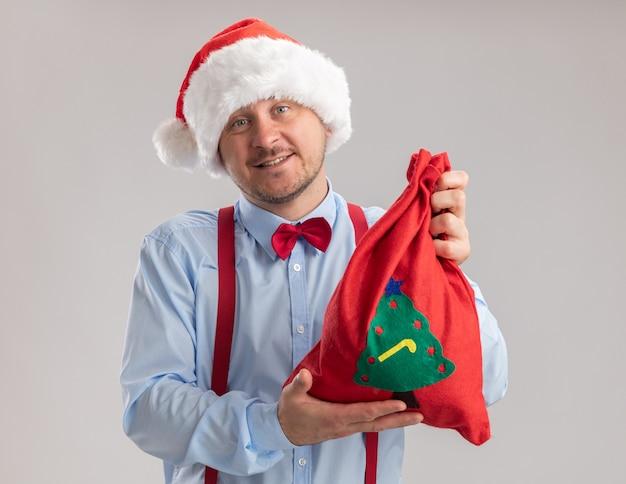 Felice giovane uomo che indossa bretelle papillon in santa hat mostrando red santa claus borsa piena di doni guardando la telecamera sorridente in piedi su sfondo bianco