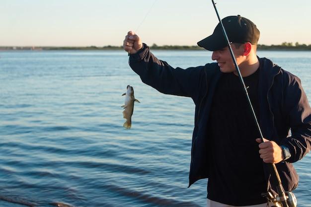 Счастливый молодой человек, который только что поймал рыбу на удочку.