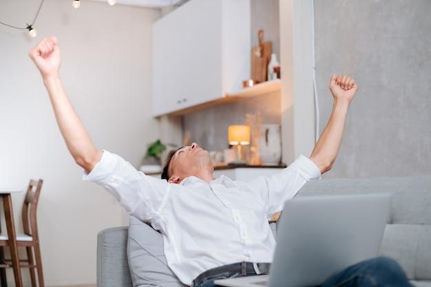 Счастливый молодой человек с ноутбуком празднует, сидя на диване