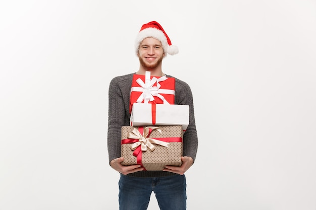 Happy young man with beard carries a lot of presents isolated on white